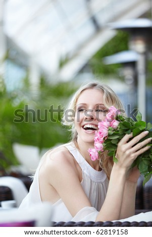 Joyful attractive girl with flowers in the restaurant - stock photo