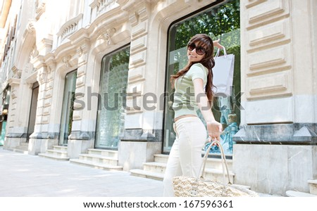 Joyful attractive young consumer woman near a shopping mall entrance with elegant buildings and stores, carrying paper bags and dancing having fun to turn at the camera smiling. - stock photo