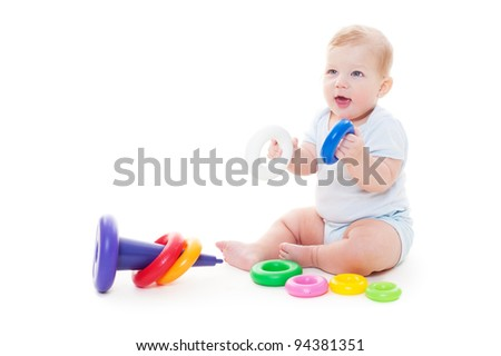 joyful baby boy sitting on floor and playing with toys. isolated on white background