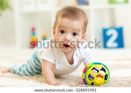 Joyful baby child crawling on the floor in nursery room - stock photo