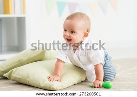 Joyful baby crawling on the floor in nursery room - stock photo