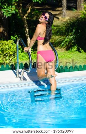 Joyful beautiful woman having fun at swimming pool stairs on summer vacation. Fit bikini girl ready to swim in fresh clean water. - stock photo