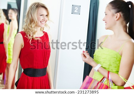 Joyful blond girl in new red dress waiting for her friend opinion in clothing department - stock photo