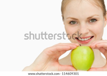 Joyful blond-haired woman presenting an apple against white background