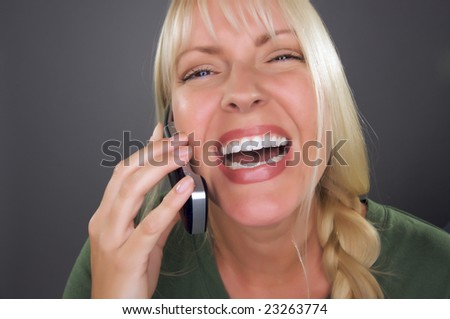 Joyful Blond Woman Using Cell Phone Against a Grey Background.