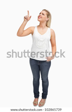 Joyful blonde woman pointing her finger up against a white background - stock photo