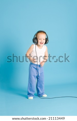 Joyful boy listening music at cord headphones over blue - stock photo
