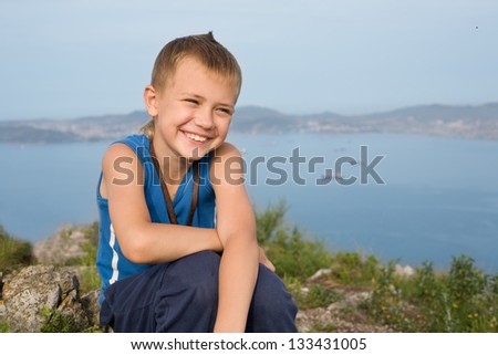 Joyful boy on top of a mountain. In the background of the sea coast - stock photo