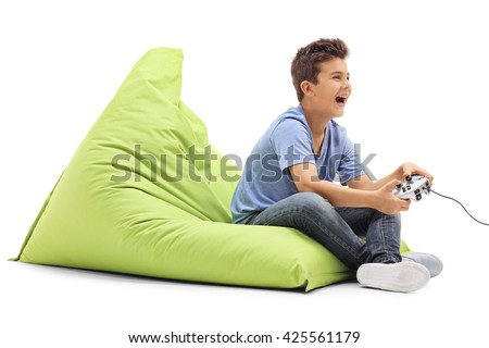 Joyful boy playing video games and laughing seated on a green beanbag isolated on white background - stock photo