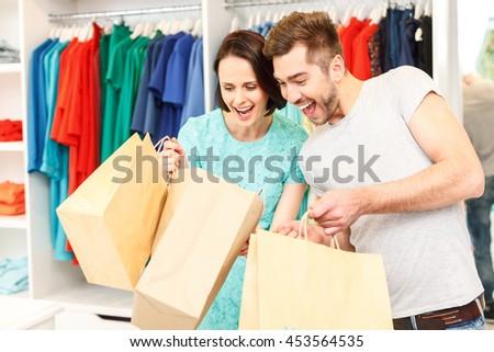 Joyful boyfriend and girlfriend purchasing in boutique - stock photo