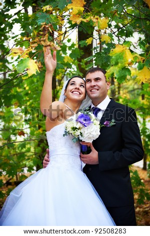 Joyful bride and groom in yellow autumn foliage on wedding walk - stock photo