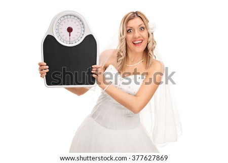 Joyful bride holding a weight scale and looking at the camera isolated on white background