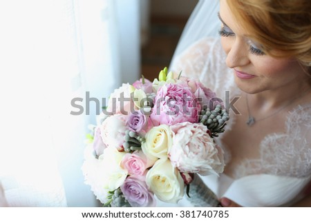 Joyful bride with veil and bridal bouquet on wedding day