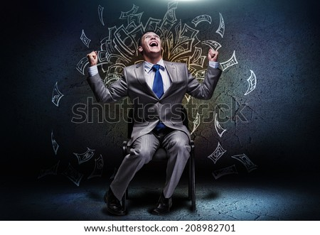Joyful businessman sitting on chair under money rain - stock photo