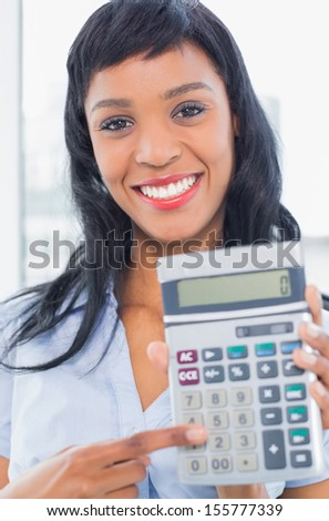 Joyful businesswoman holding a calculator in office - stock photo