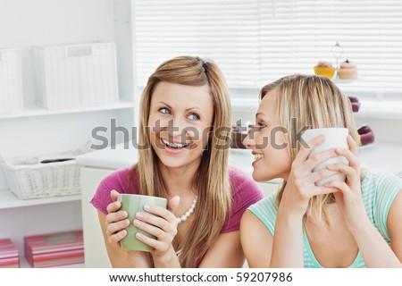 Joyful caucasian friends drinking coffee after baking in the kitchen - stock photo