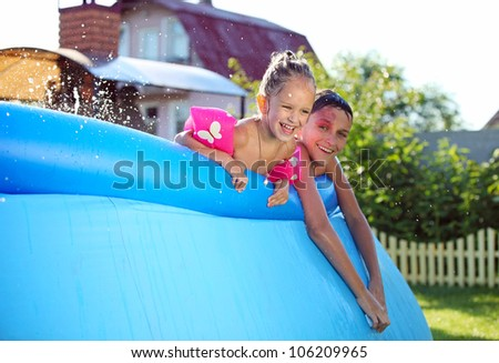 Joyful Caucasian siblings swimming in a inflatable swimming pool and looking at the camera - stock photo