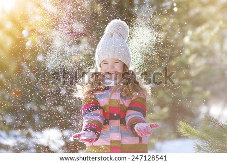 Joyful child having fun with snow in winter day - stock photo