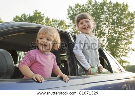 Joyful children are put out from a car window