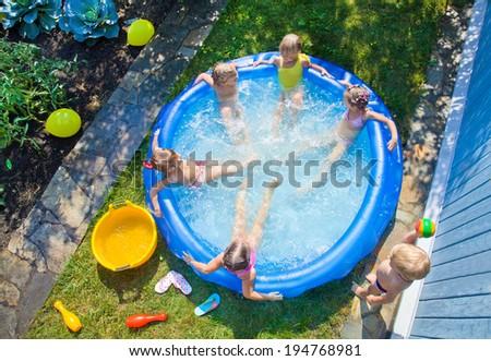 Joyful Children playing in inflatable pool - stock photo