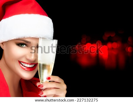 Joyful Christmas girl in Santa hat with a beautiful big smile toasting with a glass of champagne. Red lips and manicure. Happy people. Christmas greetings concept - stock photo