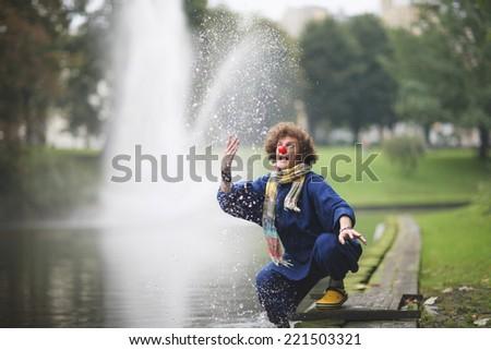 Joyful clown splashing in the city park - stock photo