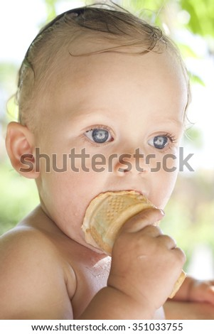 Joyful cool child girl eating ice cream outdoors near the swimming pool. Happy toddler girl with blond hair and deep blue eyes eating tasty cold sweet on a hot summer day. Portrait. Colorful photo. - stock photo