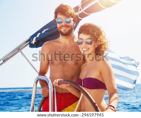 Joyful couple driving sailboat, enjoying water summer adventure, spending honeymoon in the sea cruise, romantic relationship, happy young family  - stock photo