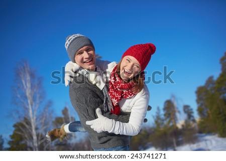 Joyful couple in knitted winterwear having fun outdoors - stock photo