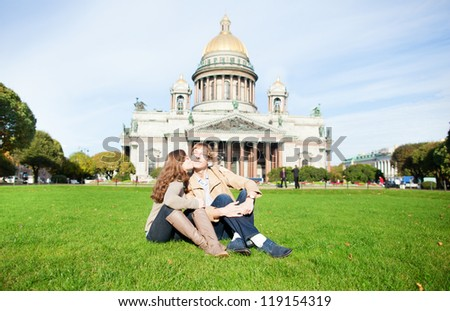 Joyful couple sitting on the grass near St. Isaac's cathedral and kissing - stock photo
