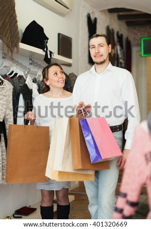 Joyful couple with shopping bags at boutique