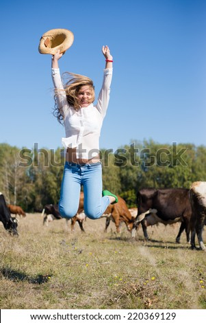 joyful cowgirl: active beautiful young woman in jeans and white shirt having fun jumping high with hat in hand among cows looking to camera on blue sky copy space background - stock photo