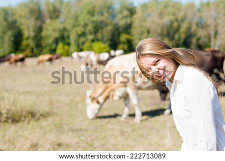 joyful cowgirl: active beautiful young woman in white shirt having fun and smiling among cows looking to camera on green forest copy space background - stock photo