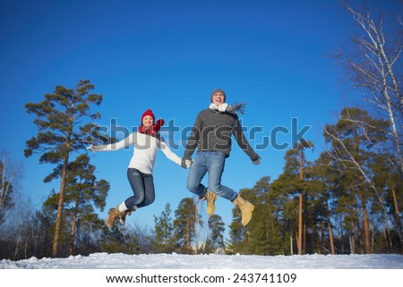 Joyful dates in knitted clothes jumping in winter park or forest - stock photo