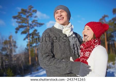 Joyful dates in knitted winterwear spending leisure outdoors - stock photo