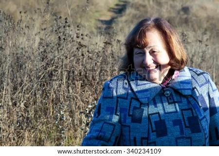 Joyful Elderly woman in a park in autumn - stock photo