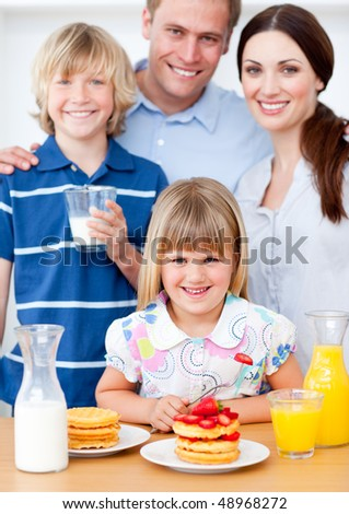 Joyful family eating breakfast in the kitchen at home - stock photo