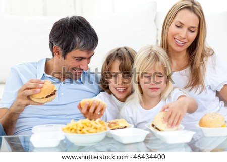 Joyful family eating hamburgers sitting on sofa