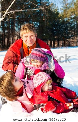 Joyful family enjoying their weekend in a winter park - stock photo