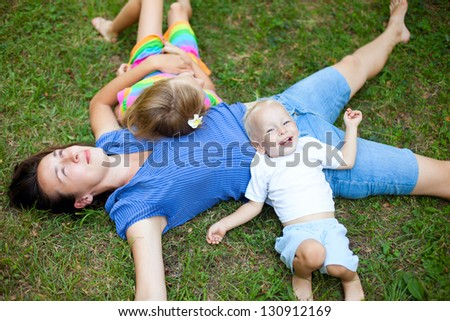 Joyful family enjoying themselves laying on the grass in a park - stock photo