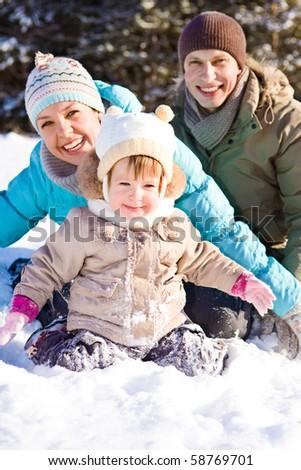 Joyful family enjoying time in winter park - stock photo