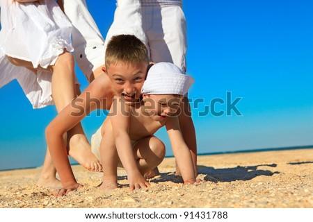 Joyful family having fun at the beach while on vacation - stock photo