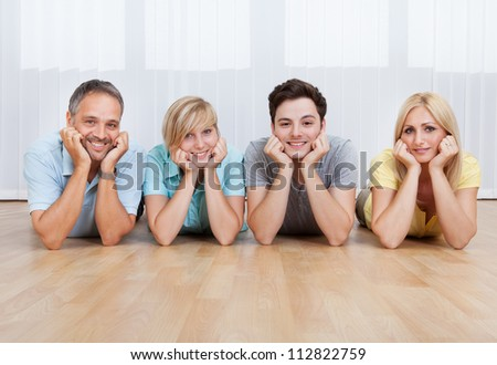 Joyful family lying on the floor with their heads close together - stock photo