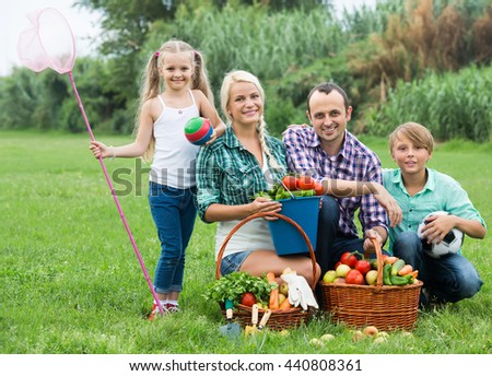 Joyful family of four spending summer day at countryside
