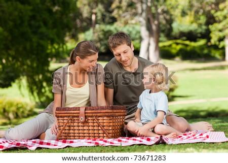 Joyful family picnicking in the park - stock photo