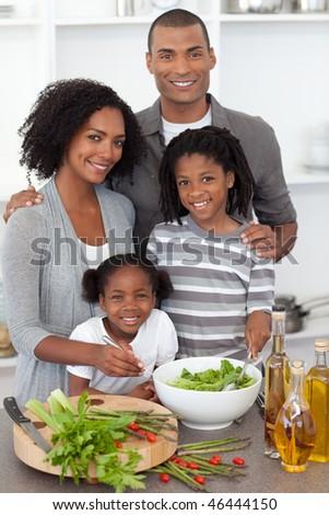 Joyful family preparing dinner in the kitchen - stock photo