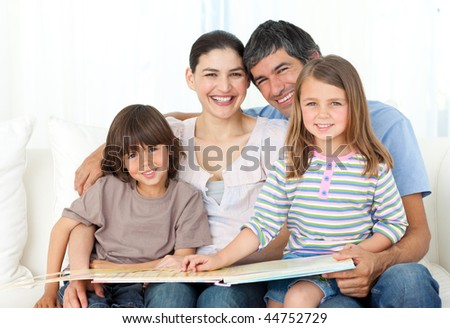 Joyful family reading together on the sofa at home - stock photo