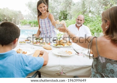 Joyful family sitting at a healthy lunch table in a holiday villa green garden, relaxing during a summer day eating fresh food and enjoying life with girl pouring juice. Outdoors eating lifestyle. - stock photo