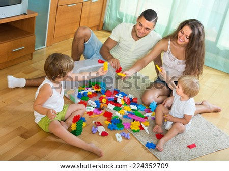 Joyful family with two little children playing with plastic toys in home