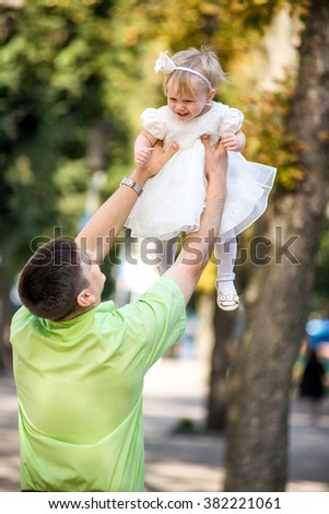 Joyful father and a cheerful child in her arms and kisses throws up. - stock photo